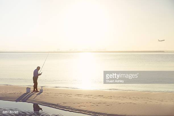 man on beach fishing on golden morning.