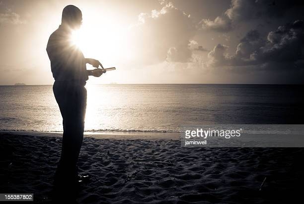 man on beach using digital tablet