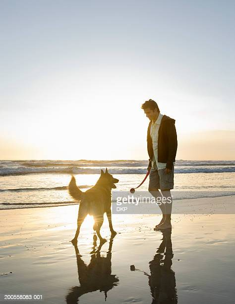 Man on beach with dog at sunset, holding ball thrower