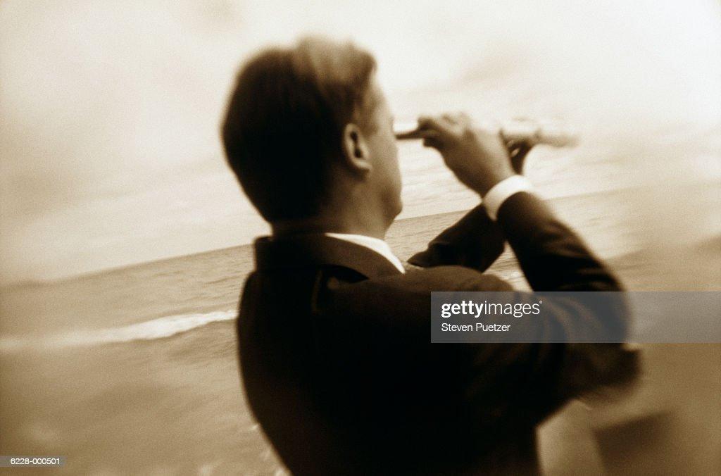 Man on Beach with Telescope : Stock Photo