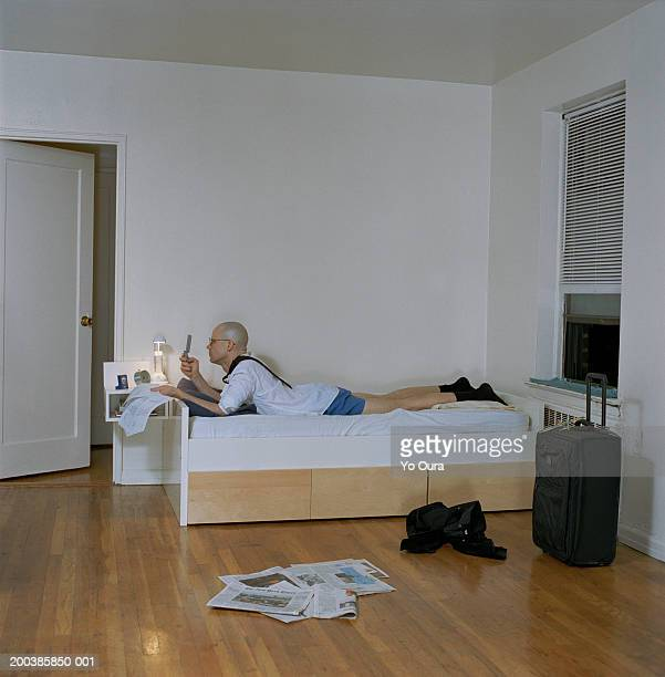 Man on bed with newspapers dialing on mobile phone, side view
