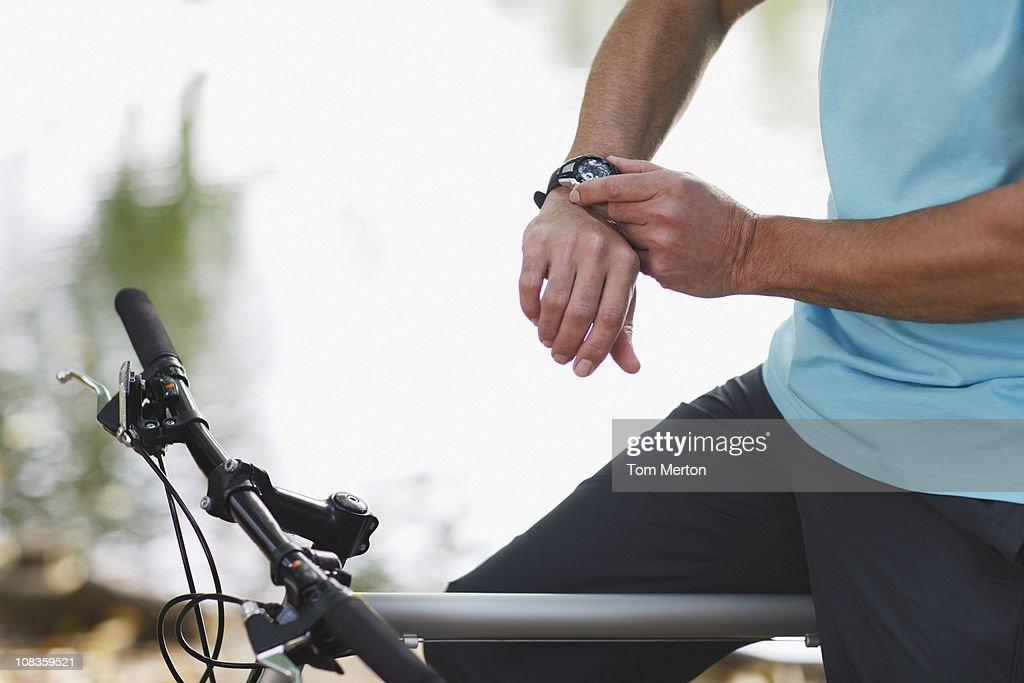 Man on bicycle checking wristwatch : Stock Photo
