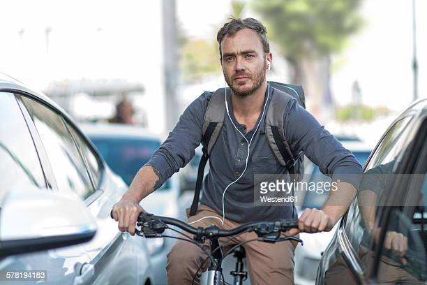 Man on bicycle in traffic jam