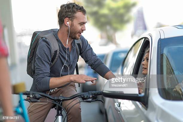 Man on bicycle talking to woman in car