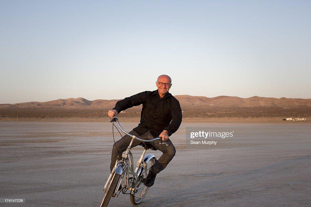 Man on bike in desert : Stock Photo