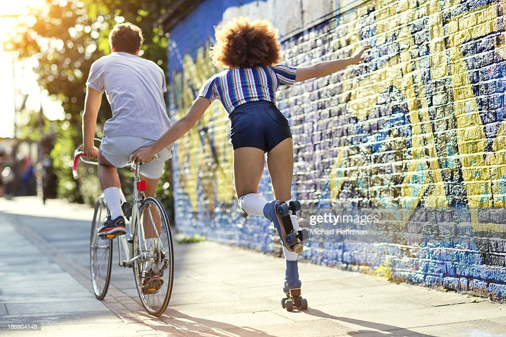 man on bike towing young woman on rollerskates
