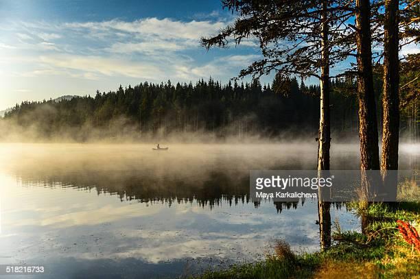 Man on boat in misty morning lake
