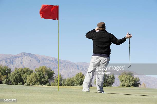 Man on cell phone at golf course