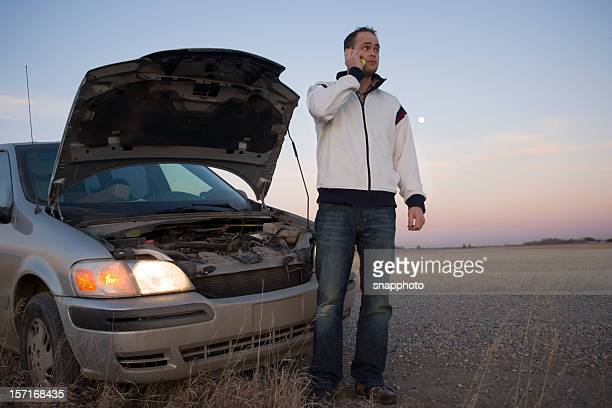 Man on cell phone in front of a broken down van at sunset