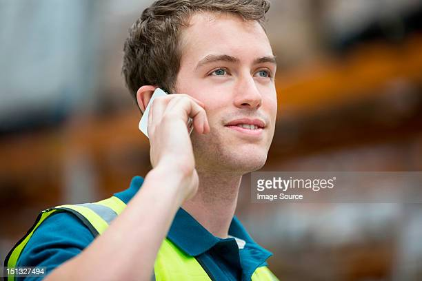 Man on cell phone in warehouse, portrait