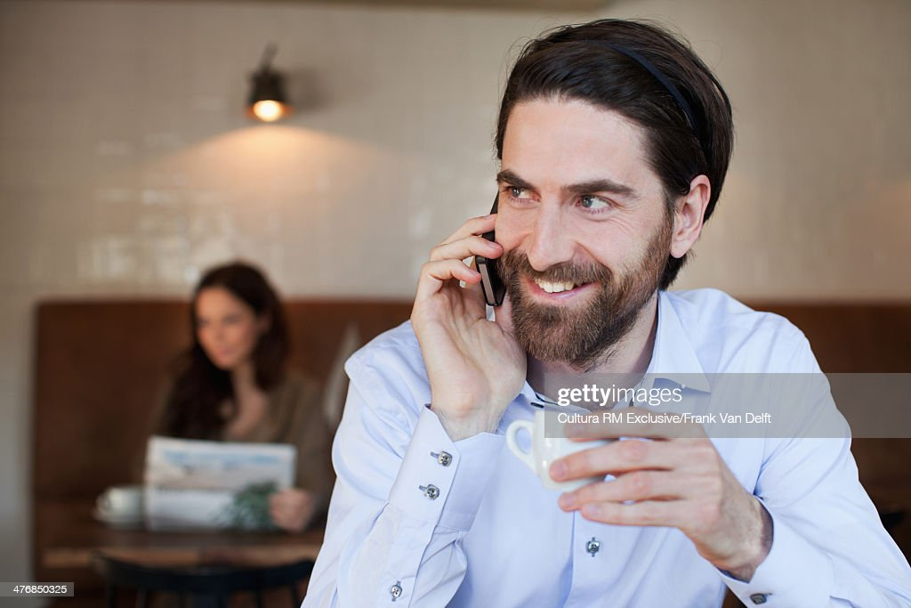 Man on cell phone with espresso in restaurant : Stock Photo