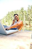 Man on cellular phone while using laptop