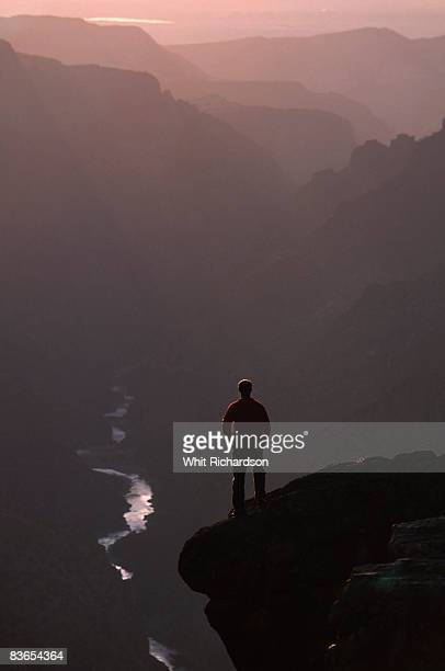 Man on cliff edge above canyon