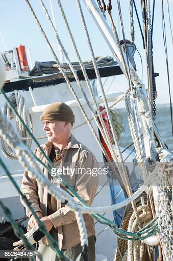 Man on commercial fishing boat putting on gloves : Photo