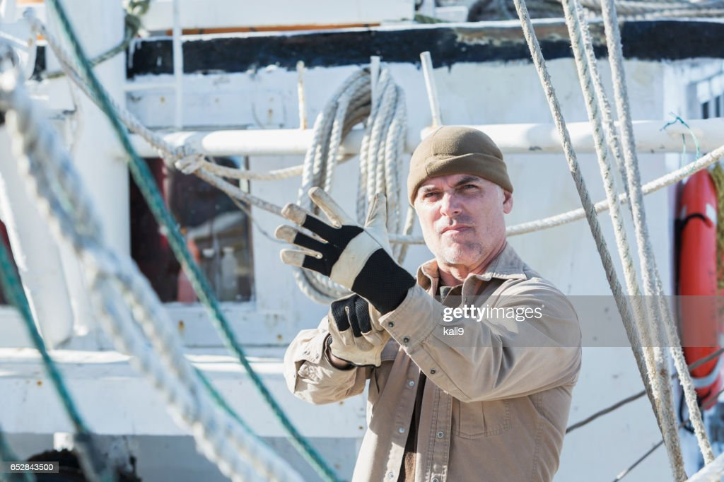 Man on commercial fishing boat putting on gloves : Stock Photo