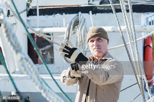 Man on commercial fishing boat putting on gloves : Stockfoto