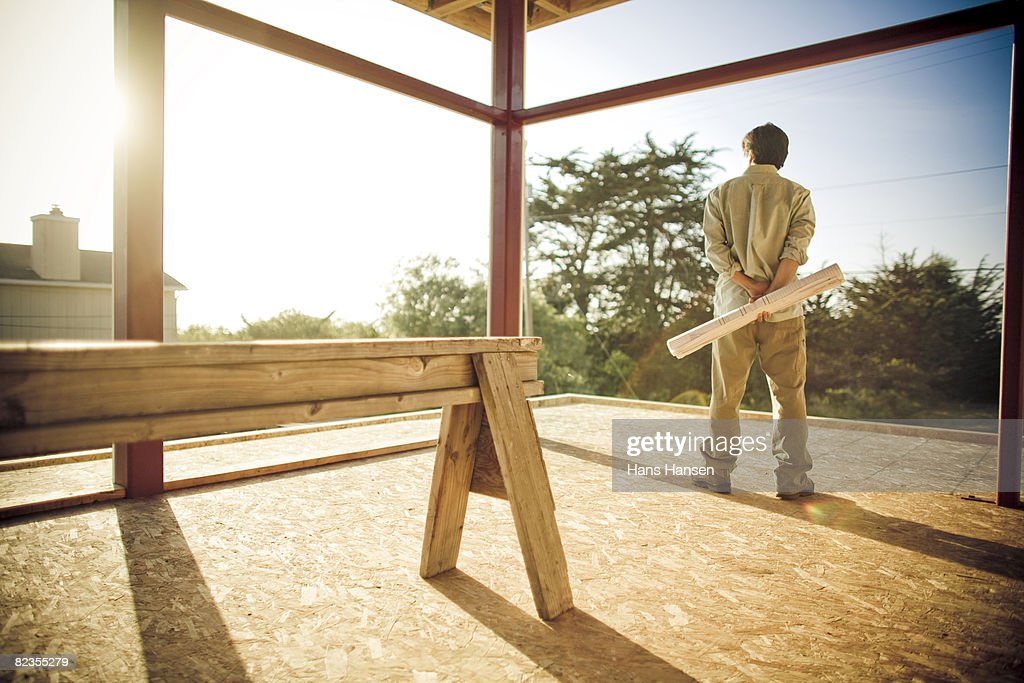 Man on construction site with plans in hand : Stock Photo