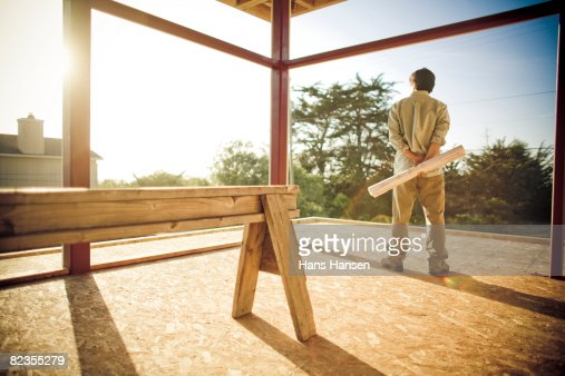 Man on construction site with plans in hand