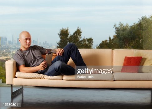 Man on couch reading on a digital tablet. : Stock Photo