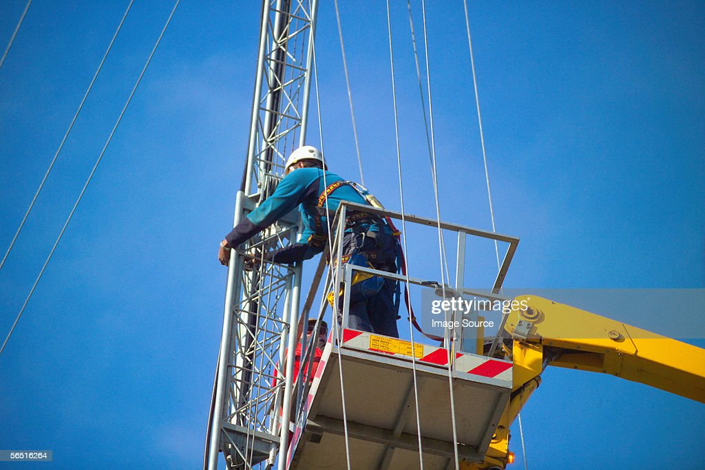 Man on crane working on mast : Stock Photo