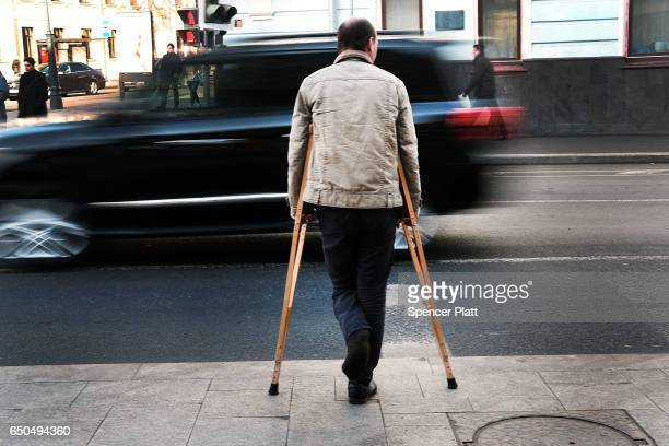 A man on crutches begs for money from passing cars on a main avenue in Moscow on March 9 2017 in Moscow Russia Relations between the United States...