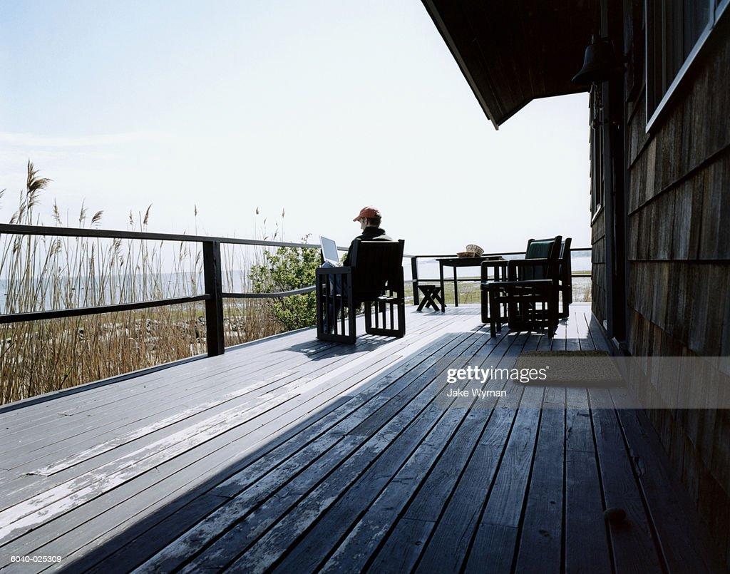 Man on Deck using Laptop : Stockfoto