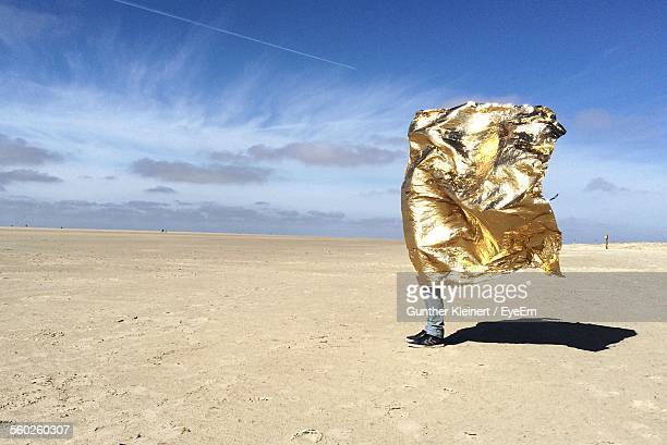 Man On Desert Protecting From Heat Being Covered With Golden Foil