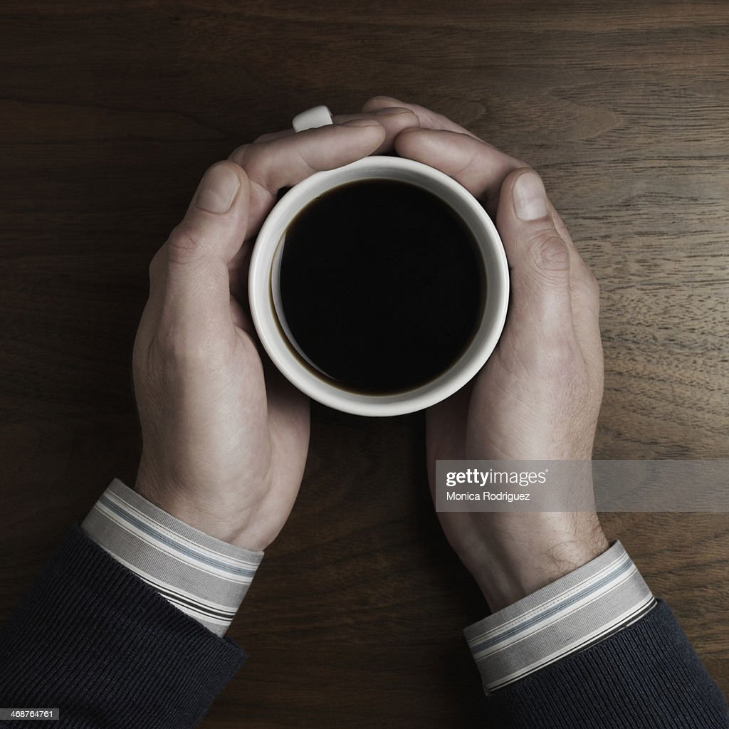 Man on desk holding cup of coffee, close up