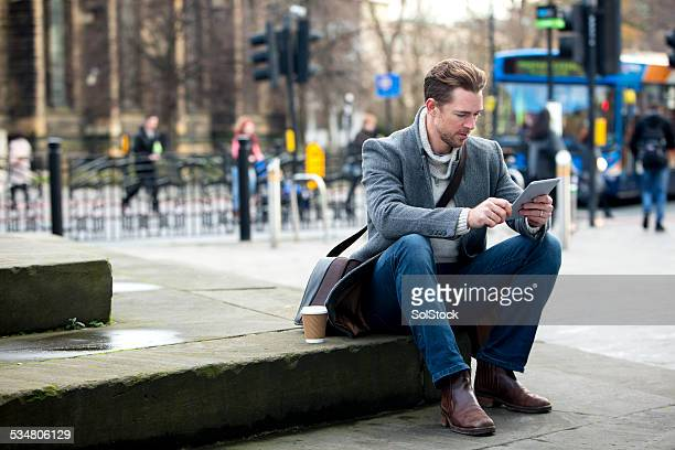 Man on Digital Tablet in the City