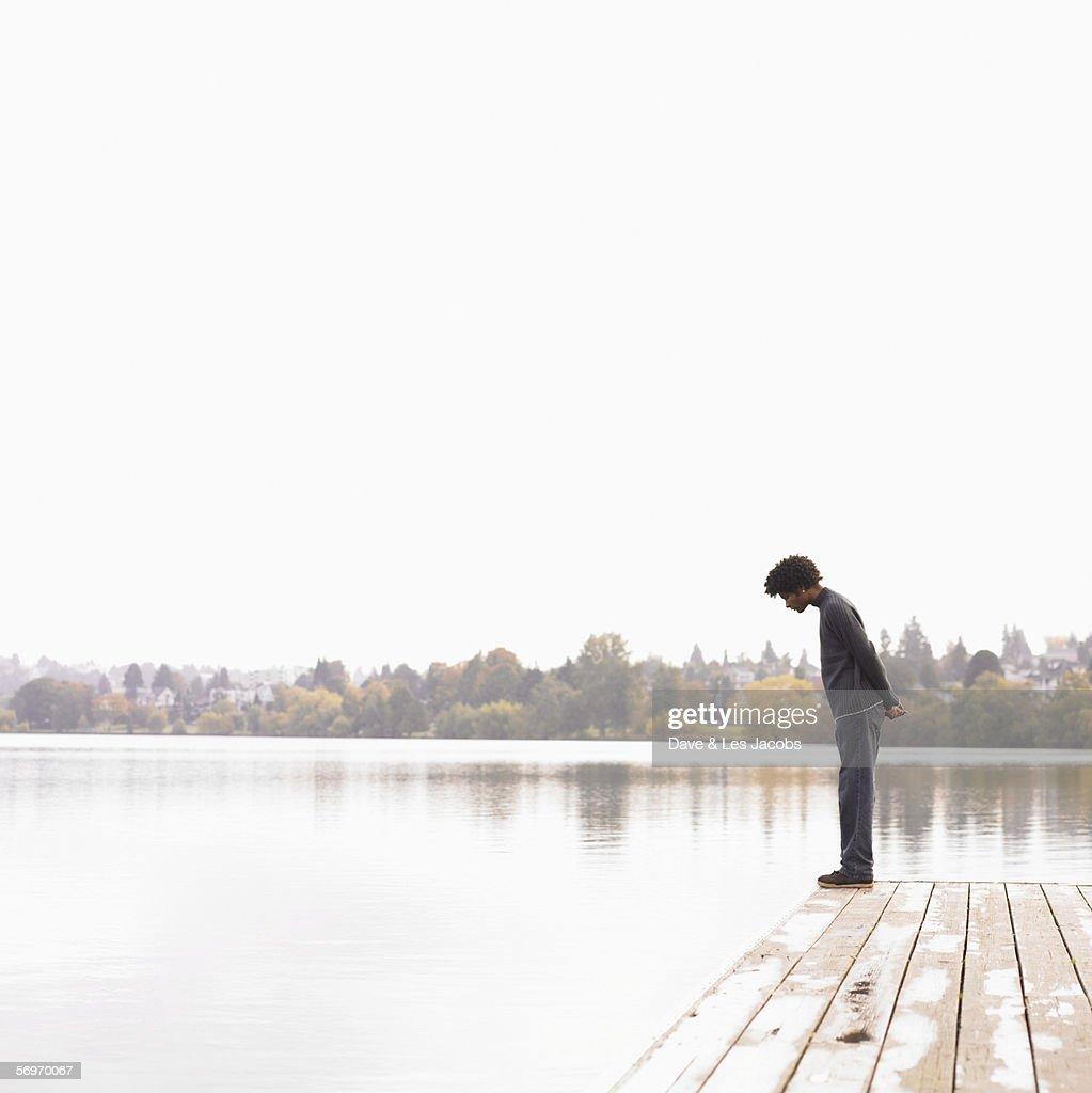 Man on dock looking into lake : Stock Photo
