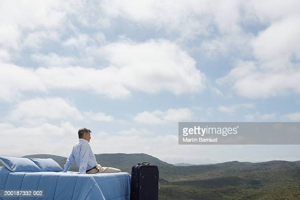 Man on double bed in rugged landscape, suitcase at end of bed