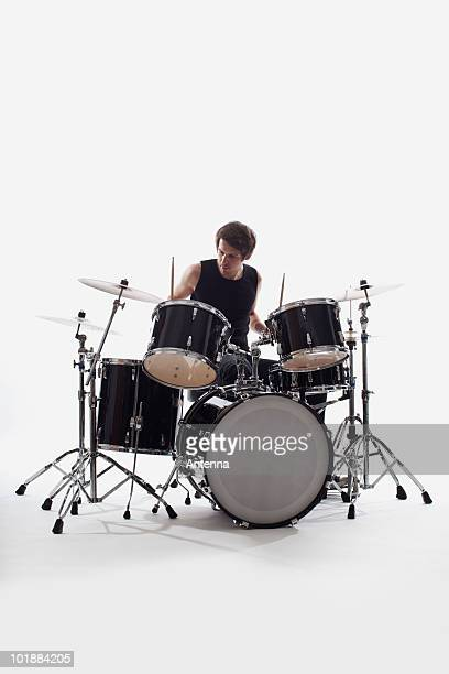A man on drums performing, studio shot, white background, back lit