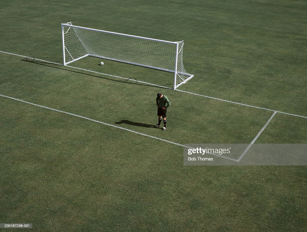 Man on empty football pitch by goal, head bowed, elevated view : Stock Photo