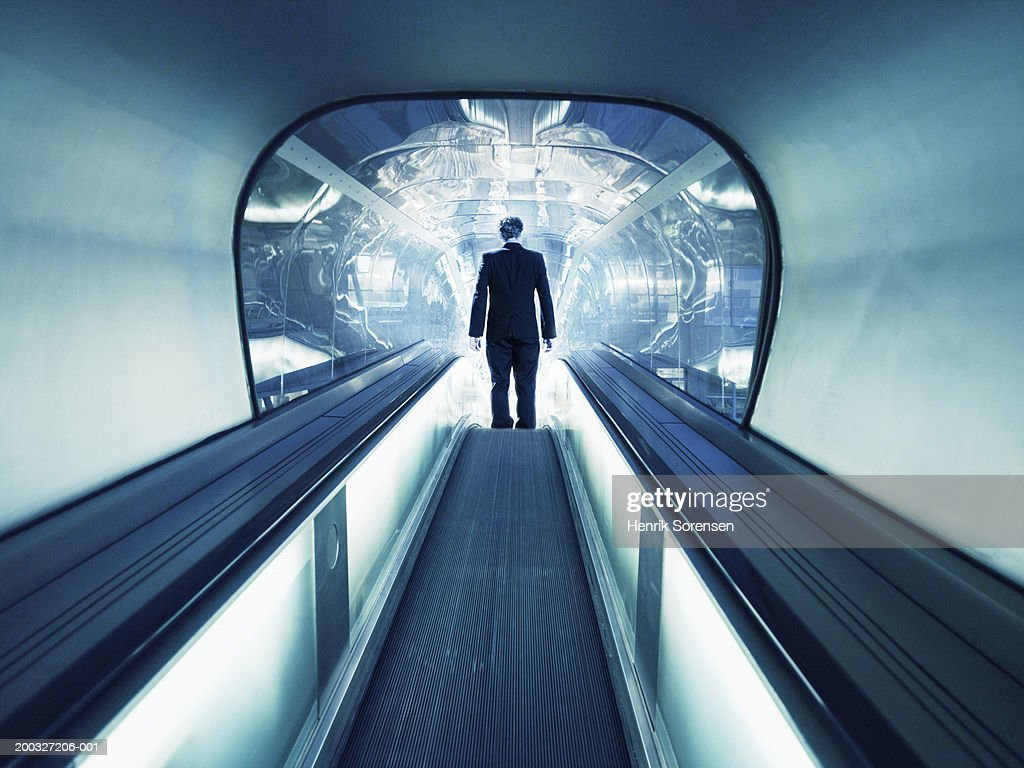 Man on escalator descending into tunnel, rear view : Stock Photo