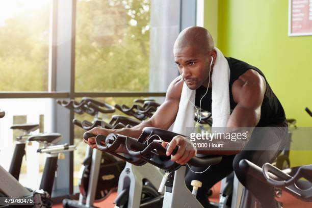 Man on exercise bike in gym, looking focused