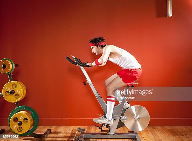 Man on exercise bike with headband and kneesocks