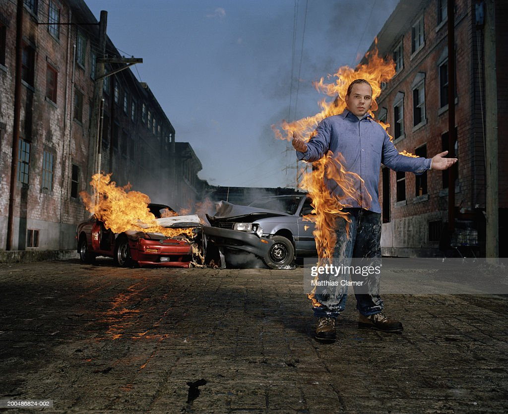 Man on fire, car collision in background : Stock Photo