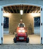 Man on garden tractor sitting in entrance of garage, portrait