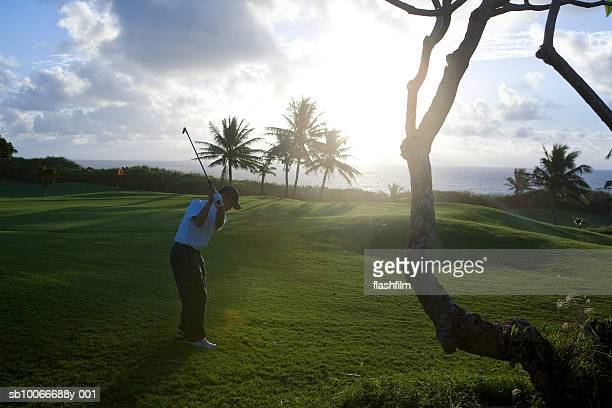 Man on golf course playing golf at dawn