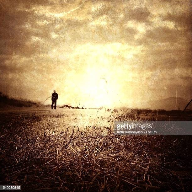 Man On Grassy Field Against Cloudy Sky