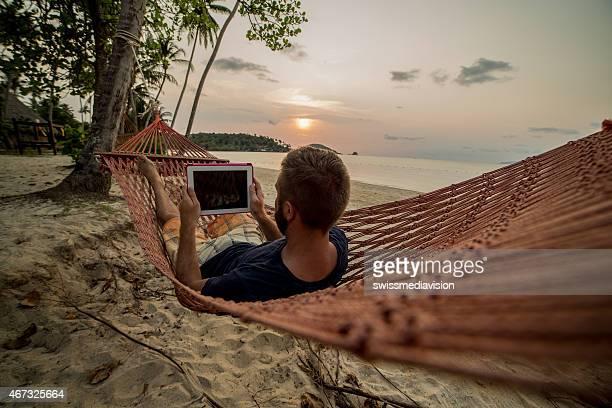 Man on hammock relaxing-Digital tablet