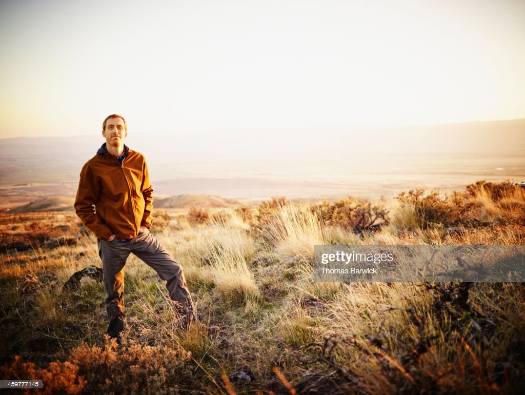 Man on hillside of desert landscape at sunset : Stock Photo