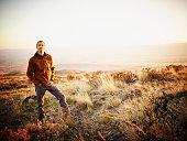 Man on hillside of desert landscape at sunset