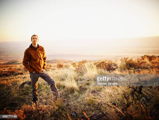 Man on hillside of desert landscape at sunset