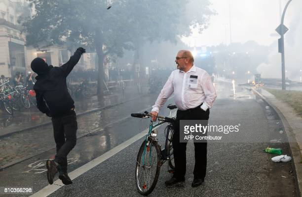 A man on his bike looks at a masked protester throwning a stone at riot police using water cannon on July 7 2017 in Hamburg northern Germany where...