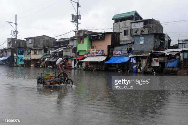 A man on his bike wades through a flooded street in Manila on June 30 2013 Tropical storm Rumbia lashed Manila and nearby areas with 6575 kph winds...