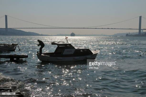 A man on his boat at a mooring on the Asian side of the Bosphorus In the background the Bosphorus Bridge can be seen