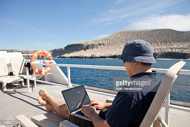 A man on his laptop on the deck of a boat