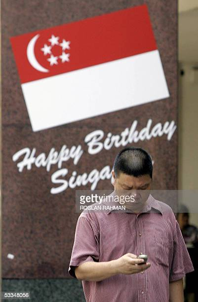 A man on his mobile phone stands in front of the Singapore flag posted on a building pillar in Singapore 10 August 2005 Singapore's economy is riding...