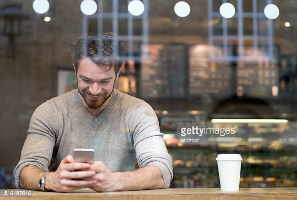 Man on his phone at a cafe